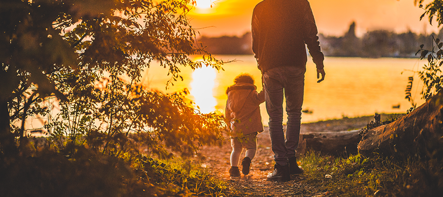 Parent and child walking forward, shaded by sunset