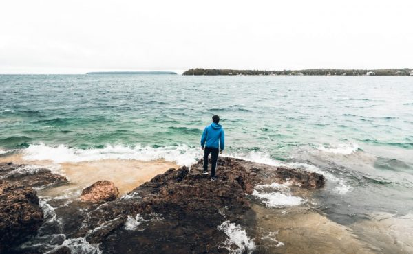 Growing With after high school - young man standing on the edge of the ocean looking outward